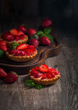 Fresh homemade berrie tarts. Fresh homemade strawberries tarts on wooden background stock images