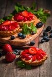 Fresh homemade berrie tarts. Fresh homemade strawberries tarts on wooden background royalty free stock image