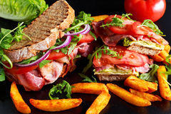 Fresh homemade BLT sandwich on grilled bread with bacon, lettuce, beef tomato, red onions, wild rocket and chips.  stock photos