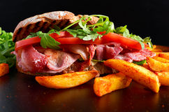 Fresh homemade BLT sandwich on grilled bread with bacon, lettuce, beef tomato, red onions, wild rocket and chips.  royalty free stock image