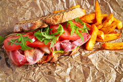 Fresh homemade BLT sandwich on grilled bread with bacon, lettuce, beef tomato, red onions, wild rocket and chips.  royalty free stock images
