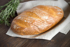Fresh homemade bread with crust on a dark wooden table. Stock Photo