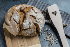 Fresh homemade bread with cumin and sunflower seeds on a wooden cutting board and a bit of risky flour Stock Images