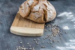 Fresh homemade bread with cumin and sunflower seeds on a wooden cutting board and a bit of risky flour Royalty Free Stock Photography