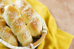 Fresh homemade bread rolls with sesam seed in basket on wooden t Stock Photo