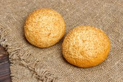 Fresh homemade bread rolls with sesam seeds on wooden table.  Royalty Free Stock Photo