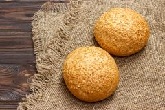 Fresh homemade bread rolls with sesam seeds on wooden table.  Stock Photos