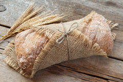Fresh homemade bread  and wheat ears on old table. Royalty Free Stock Image