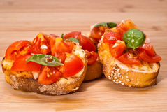 Fresh homemade bruschette. Fresh homemade crispy Italian appetizer called Bruschetta topped with tomato, garlic and basil on wooden board Royalty Free Stock Photography
