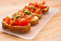 Fresh homemade bruschette. Fresh homemade crispy Italian appetizer called Bruschetta topped with tomato, garlic and basil on wooden board Royalty Free Stock Photo