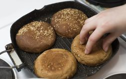 Fresh homemade buns for burgers, fried in a pan, the girl overturns them. royalty free stock image