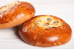 Fresh homemade buns. Two fresh homemade buns with cottage cheese and raisins on a wooden table Stock Image
