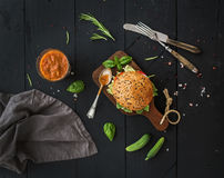 Fresh homemade burger on dark serving board with spicy tomato sauce, sea salt and herbs over black wooden background. Fresh homemade burger on dark serving board royalty free stock photography