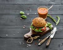 Fresh homemade burger on dark serving board with Stock Image