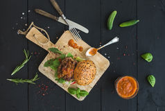 Fresh homemade burger on dark serving board with spicy tomato sauce, sea salt Royalty Free Stock Images
