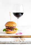 Fresh homemade burger on wooden serving board with onion rings and glass of red wine Stock Photography