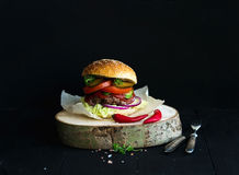 Fresh homemade burger on wooden serving board with Stock Photo