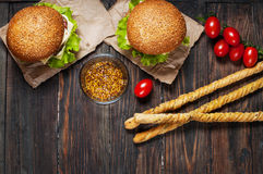 Fresh homemade burgers and breadsticks on wooden background Royalty Free Stock Photo
