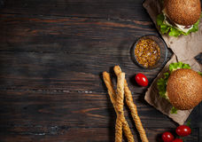 Fresh homemade burgers and breadsticks on wooden background Stock Photography