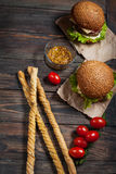 Fresh homemade burgers and breadsticks on wooden background Stock Image