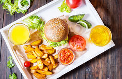 Fresh homemade burgers, fried potatoes, beer and juice served on white tray stock photo
