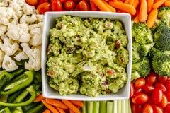 Fresh Homemade Chunky Guacamole Dip. Bowl of homemade chunky guacamole surrounded by fresh vegetables Stock Photography