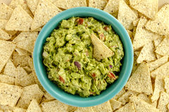 Fresh Homemade Chunky Guacamole Dip. Homemade chunky guacamole in bright blue bowl surrounded by white corn tortilla chips Royalty Free Stock Images