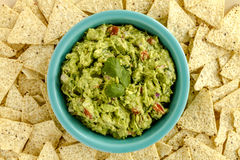 Fresh Homemade Chunky Guacamole Dip. Homemade chunky guacamole in bright blue bowl surrounded by white corn tortilla chips Royalty Free Stock Photo