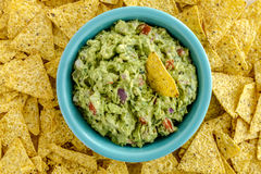 Fresh Homemade Chunky Guacamole Dip. Homemade chunky guacamole in bright blue bowl surrounded by yellow corn tortilla chips Royalty Free Stock Photos