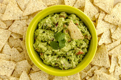 Fresh Homemade Chunky Guacamole Dip. Homemade chunky guacamole in bright green bowl surrounded by white corn tortilla chips Royalty Free Stock Image