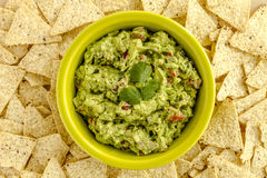 Fresh Homemade Chunky Guacamole Dip. Homemade chunky guacamole in bright green bowl surrounded by white corn tortilla chips Stock Image