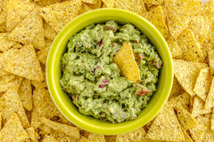 Fresh Homemade Chunky Guacamole Dip. Homemade chunky guacamole in bright green bowl surrounded by yellow corn tortilla chips Stock Photos