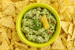 Fresh Homemade Chunky Guacamole Dip. Homemade chunky guacamole in bright green bowl surrounded by yellow corn tortilla chips Stock Photography