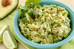 Fresh Homemade Chunky Guacamole Dip. Close up of homemade chunky guacamole in bright blue bowl sitting on green napkin with lime wedges and avocado half Stock Images
