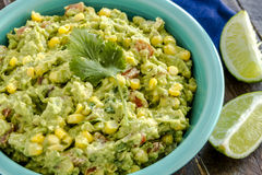 Fresh Homemade Chunky Guacamole Dip. Close up of homemade chunky guacamole with fresh corn in bright blue bowl and lime wedges sitting on blue napkin Royalty Free Stock Images