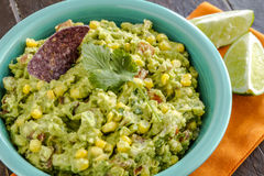 Fresh Homemade Chunky Guacamole Dip. Close up of homemade chunky guacamole with fresh corn in bright blue bowl and lime wedges sitting on orange napkin Stock Photo