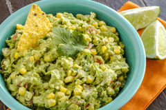 Fresh Homemade Chunky Guacamole Dip. Close up of homemade chunky guacamole with fresh corn in bright blue bowl and lime wedges sitting on orange napkin Stock Images
