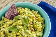 Fresh Homemade Chunky Guacamole Dip. Close up of homemade chunky guacamole with fresh corn in bright blue bowl sitting on dark blue napkin Stock Photos
