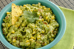 Fresh Homemade Chunky Guacamole Dip. Close up of homemade chunky guacamole with fresh corn in bright blue bowl and sitting on green napkin Stock Photo
