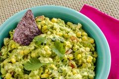 Fresh Homemade Chunky Guacamole Dip. Close up of homemade chunky guacamole with fresh corn in bright blue bowl sitting on pink napkin Stock Photos