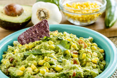 Fresh Homemade Chunky Guacamole Dip. Close up of homemade chunky guacamole with fresh corn in bright blue bowl surrounded by fresh ingredients Royalty Free Stock Image