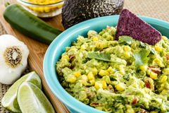 Fresh Homemade Chunky Guacamole Dip. Close up of homemade chunky guacamole with fresh corn in bright blue bowl surrounded by fresh ingredients Royalty Free Stock Photos