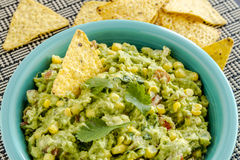 Fresh Homemade Chunky Guacamole Dip. Close up of homemade chunky guacamole with fresh corn in bright blue bowl and yellow corn torilla chips Royalty Free Stock Images