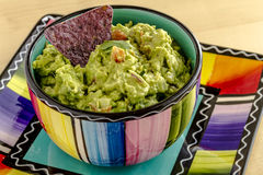 Fresh Homemade Chunky Guacamole Dip. Homemade chunky guacamole in colorful bowl garnished with blue corn tortilla chip and cilantro Stock Images