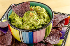 Fresh Homemade Chunky Guacamole Dip. Homemade chunky guacamole in colorful bowl garnished with blue corn tortilla chip and cilantro Stock Photo