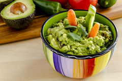 Fresh Homemade Chunky Guacamole Dip. Fresh chunky guacamole in colorful bowl garnished with raw carrots and green peppers and cilantro Stock Image