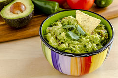 Fresh Homemade Chunky Guacamole Dip. Fresh chunky guacamole in colorful bowl garnished with white corn tortilla chip and cilantro Royalty Free Stock Images