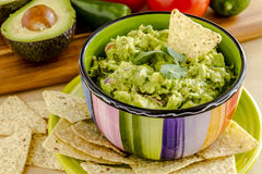 Fresh Homemade Chunky Guacamole Dip. Fresh chunky guacamole in colorful bowl garnished with white corn tortilla chip and cilantro Royalty Free Stock Photos