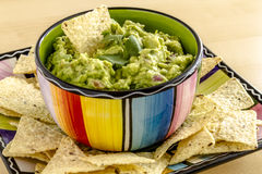 Fresh Homemade Chunky Guacamole Dip. Homemade chunky guacamole in colorful bowl garnished with white corn tortilla chip and cilantro Stock Photo
