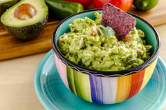 Fresh Homemade Chunky Guacamole Dip. Fresh chunky guacamole in colorful bowl sitting on bright blue plate garnished with blue tortilla chip and cilantro Royalty Free Stock Photo